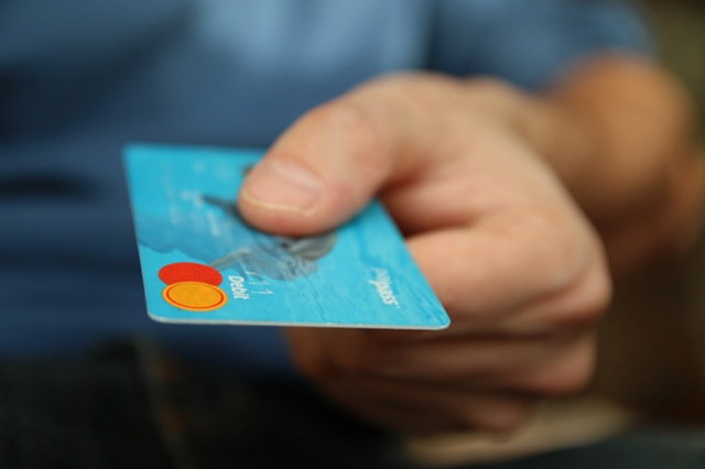 Image of a hand offering a credit card.