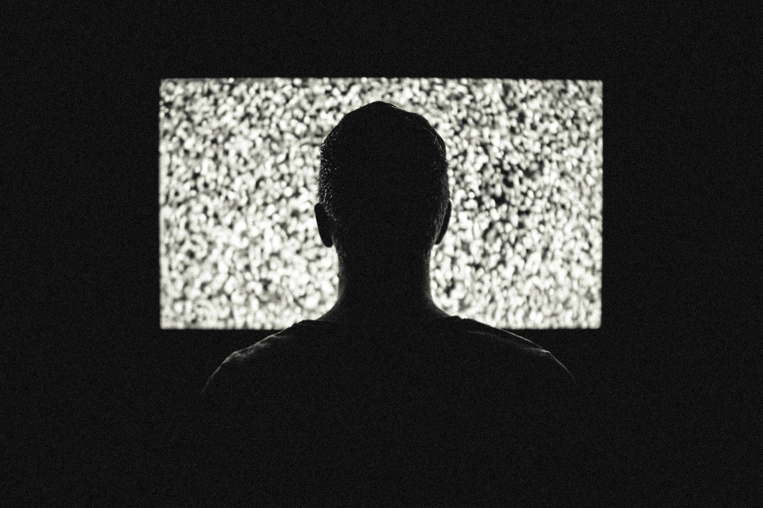 silhouetted man watching a television screen of static