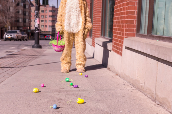 Man in Easter bunny suit with Easter basket, stands above plastic eggs that have spilt on the ground.