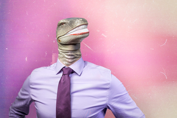 Man in suit where the head has been replaced by a toy reptile head.