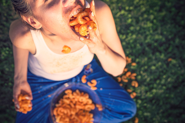Man stuffing cheese puffs into his already full mouth with cheese puffs falling on the ground below him.